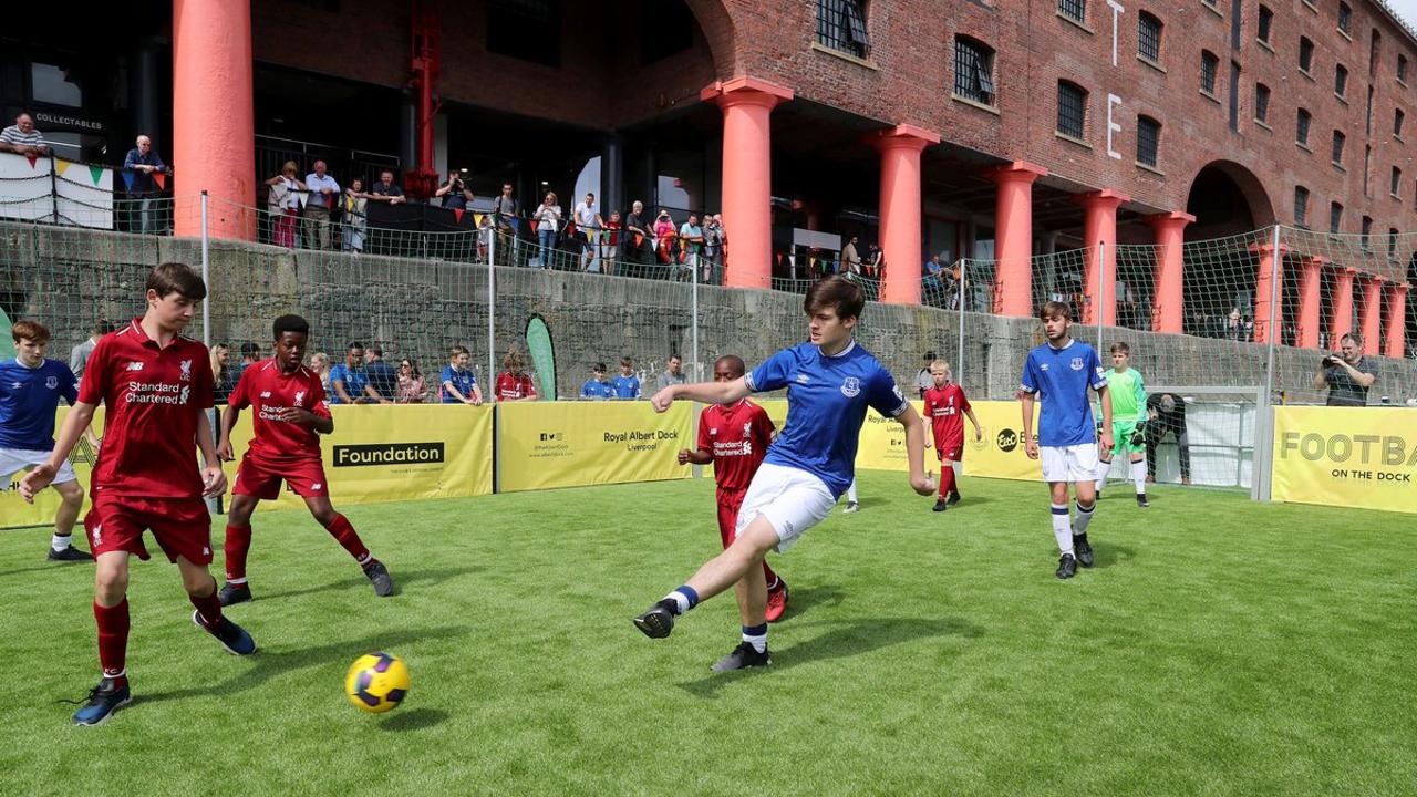 Children play football at the Albert Docks