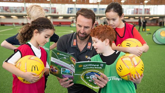 Sponsorship of Sport - Gareth Southgate shows children a FA-endorsed McDonalds workbook